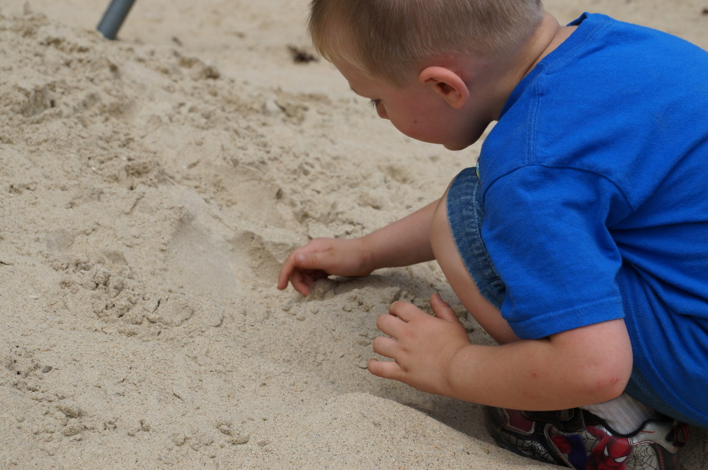 digging in the sand at the playground